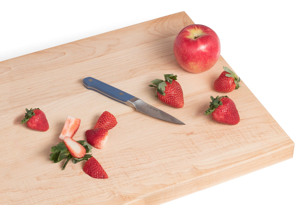 A cutting board with fruit and a paring knife, one of the essential types of kitchen knives