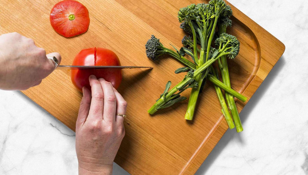 How to clean a wooden cutting board: A hand chops tomato on cutting board with rapini