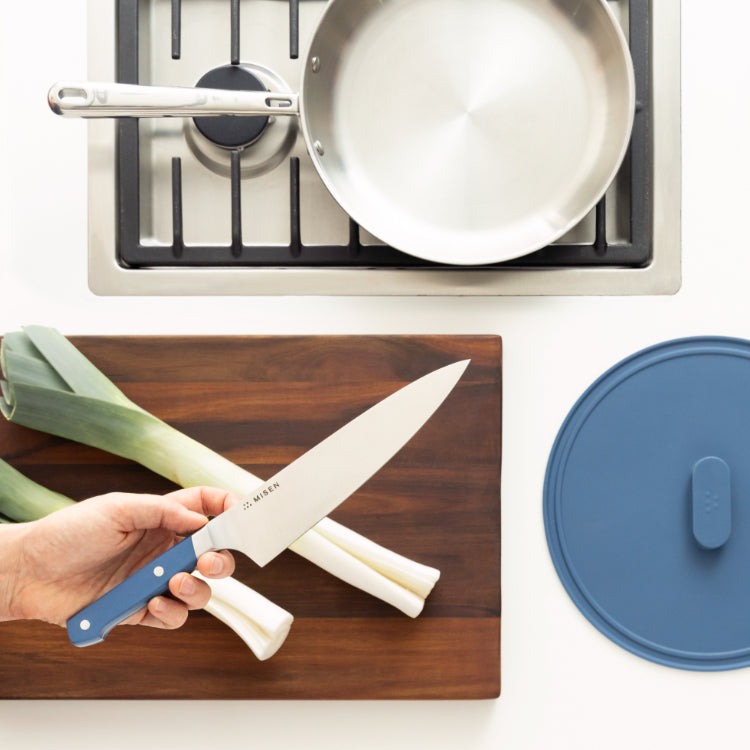 Incredible tools; assortment of Misen tools including from the left a paring knife, spatula, cutting board in acacia, chef's knife, nonstick pan, and stainless skillet with lid