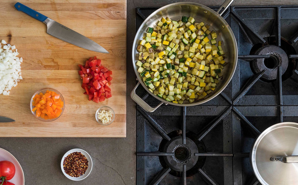 How to cook with stainless steel: chopped vegetables on a cutting board and in a stainless steel pan
