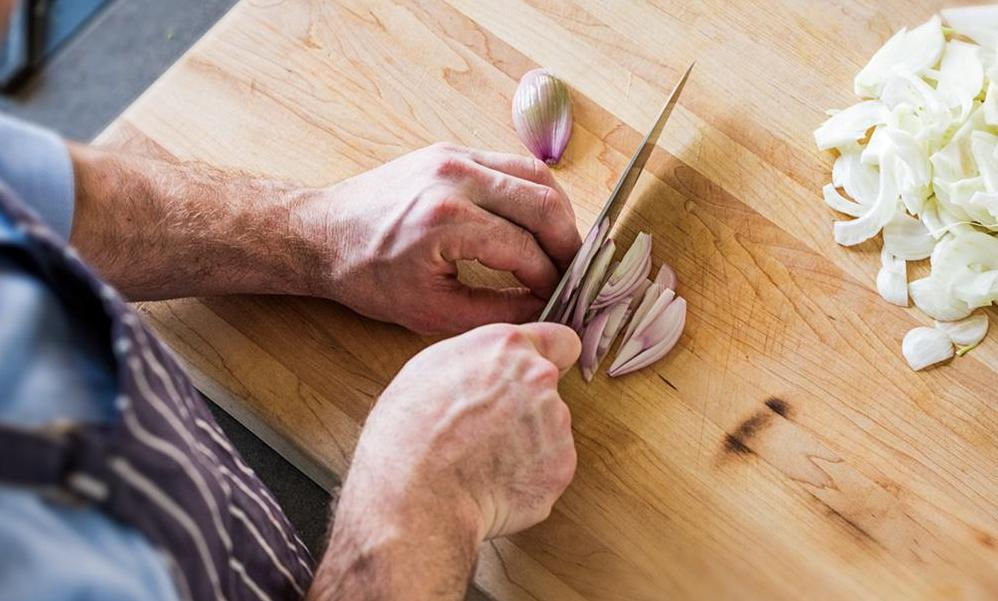 A home cook slices shallots with a santoku knife, one of the more useful types of kitchen knives