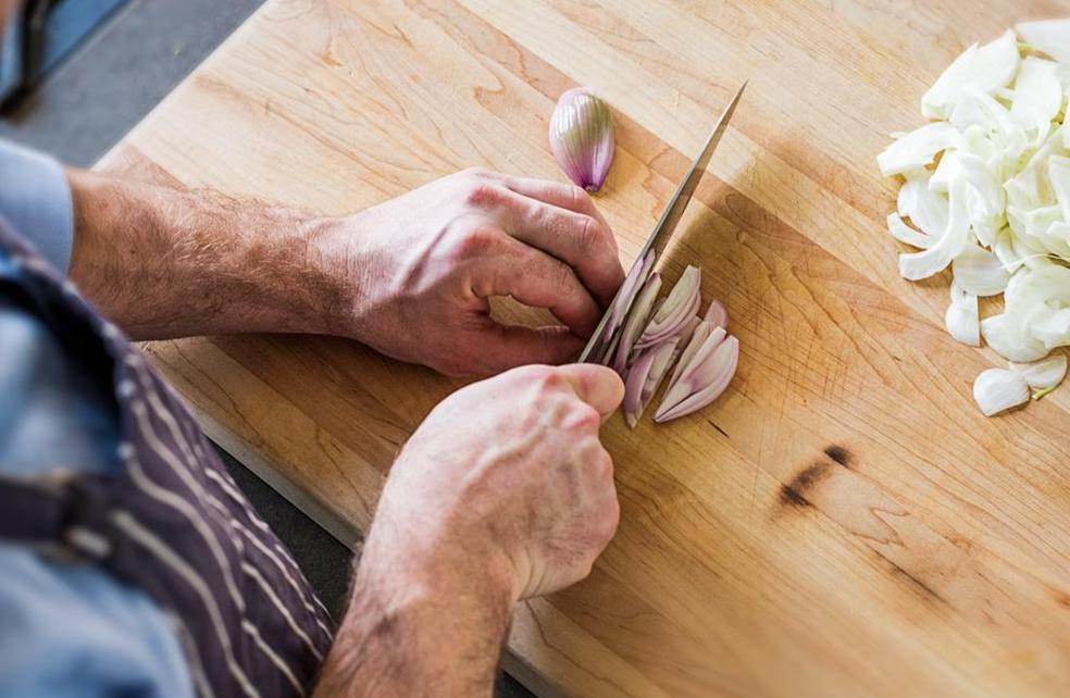 Knife shapes: A chef chops shallots