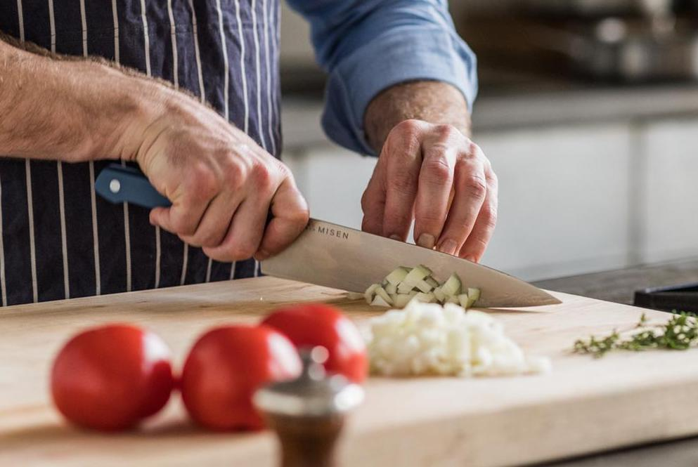 A home chops onions with a chef's knife, one of the essential types of kitchen knives