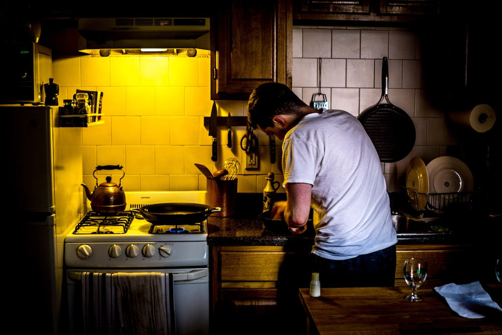 Best stainless steel cookware: A man cooks in a rustic kitchen