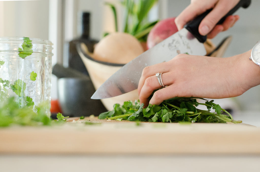 Chefs knives: A woman chops cilantro