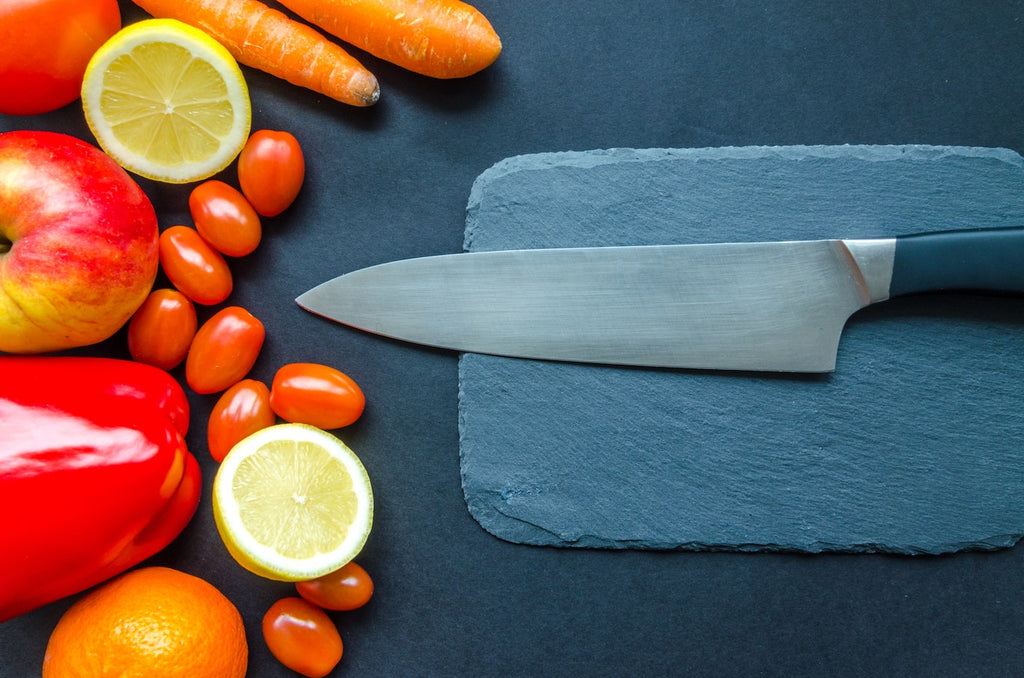 Knife tang: a chef's knife on a slate cutting board next to vegetables