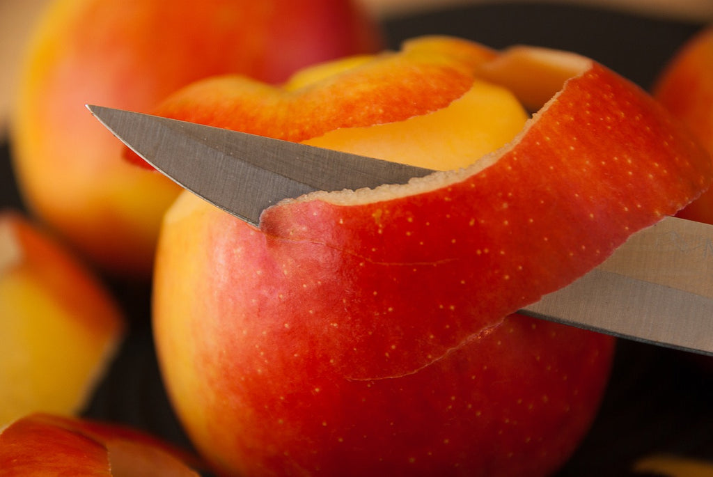How to sharpen kitchen knives: a paring knife peels an apple