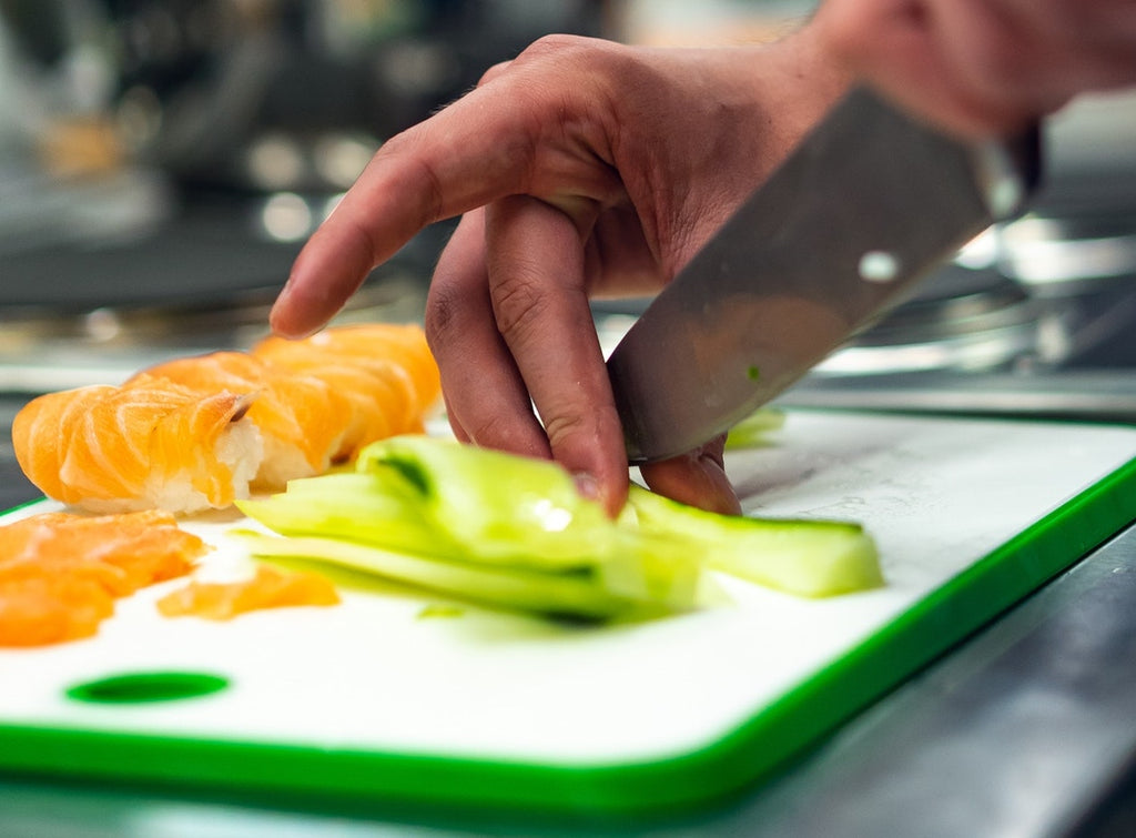 Cutting board material: Hands slice cucumber on a plastic cutting board