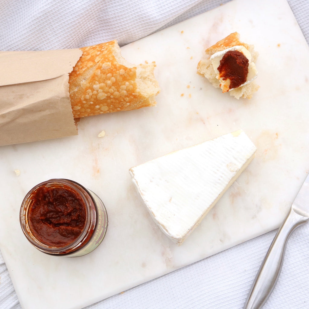 Cutting board material: bread, jam, and cheese on a marble cutting board