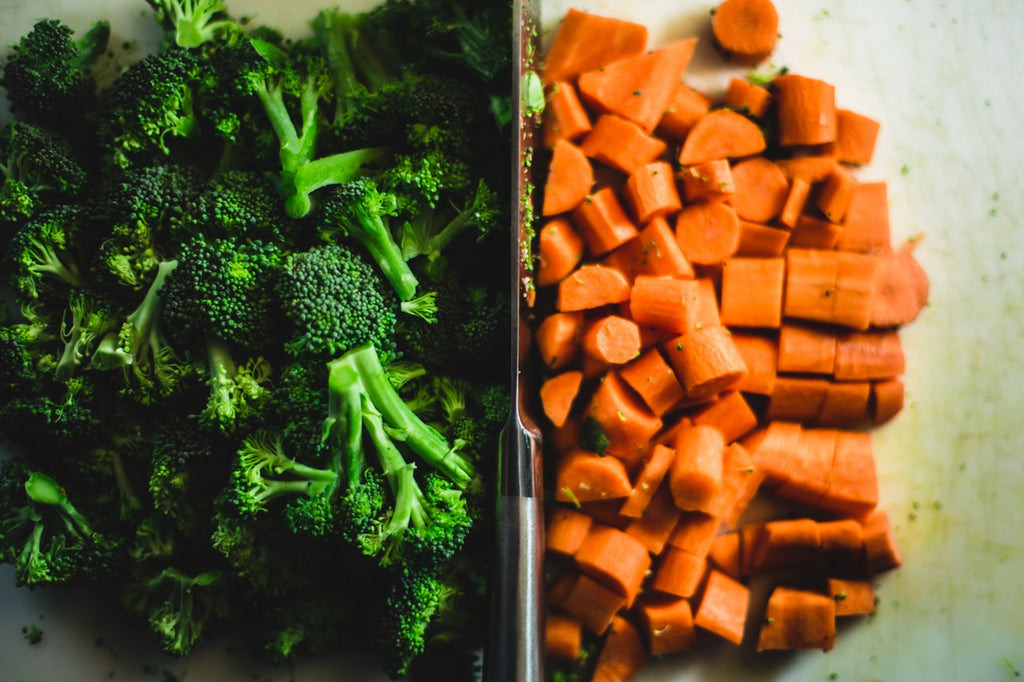 Knife sharpening: A knife separates a pile of broccoli from a pile of carrots