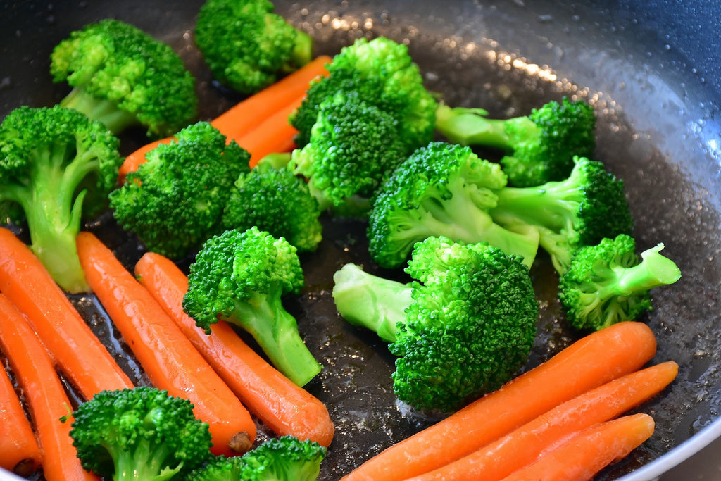 Carrots and broccoli being sautéd