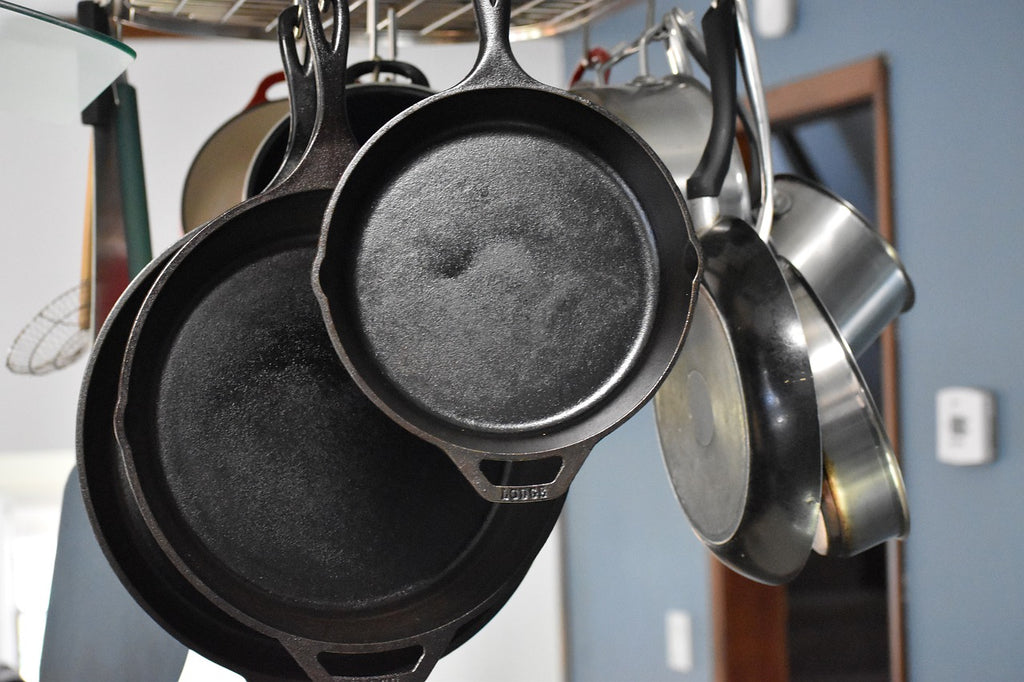 Ceramic vs. Teflon: A mix of pots and pans hang in a kitchen