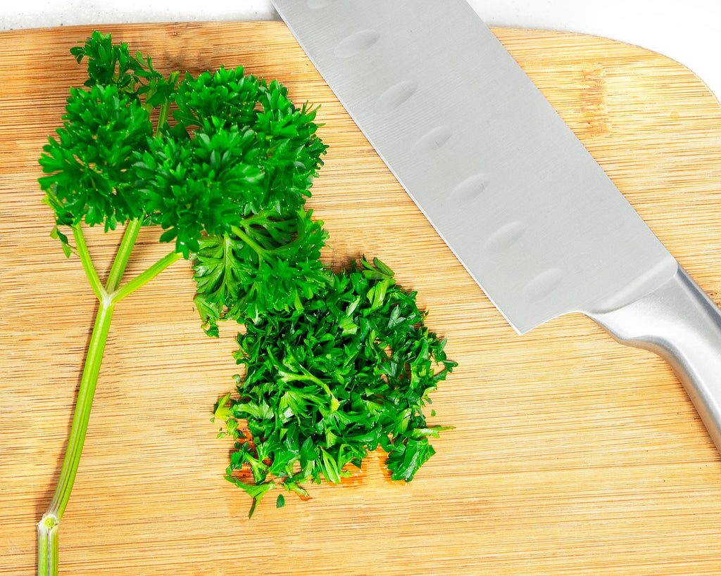 Full tang knife: a knife on a cutting board with parsley