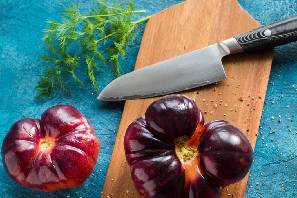 Santoku knife: a santoku on a cutting board with heirloom tomatoes