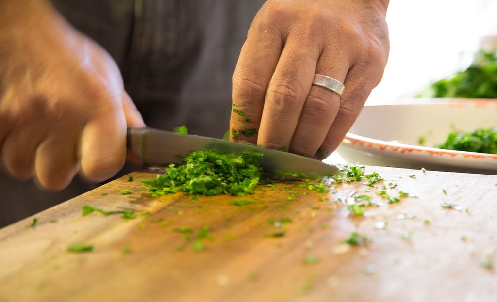 Knife block: A man chops parsley