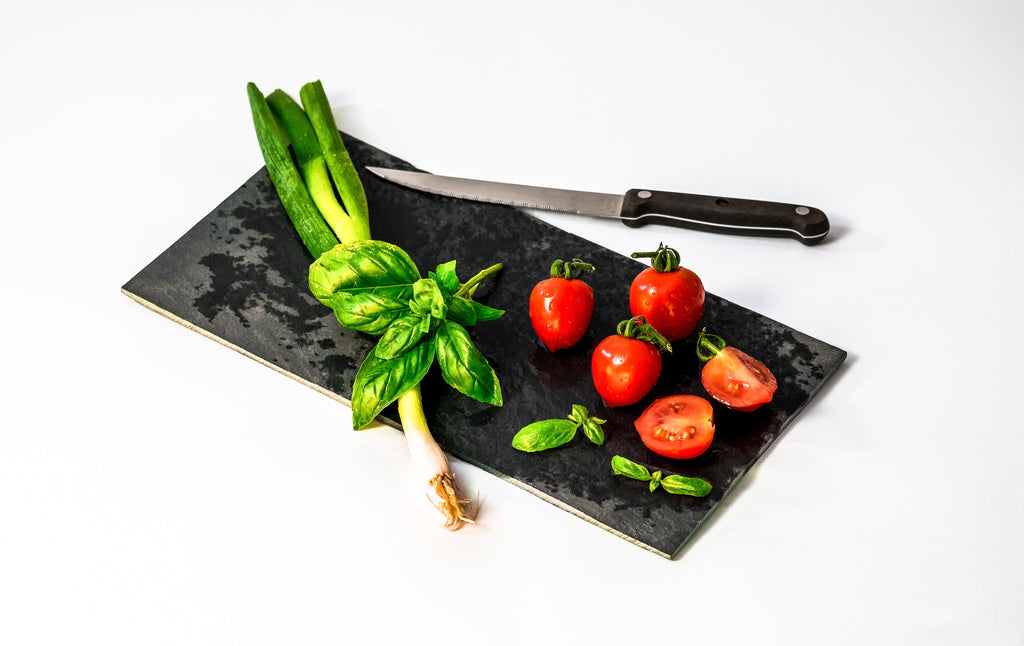 Best bread knife: a serrated knife on a cutting board with tomatoes and herbs
