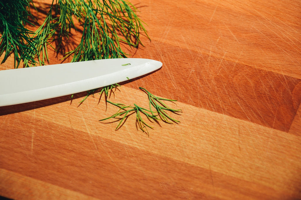 A knife blade and dill on a large cutting board