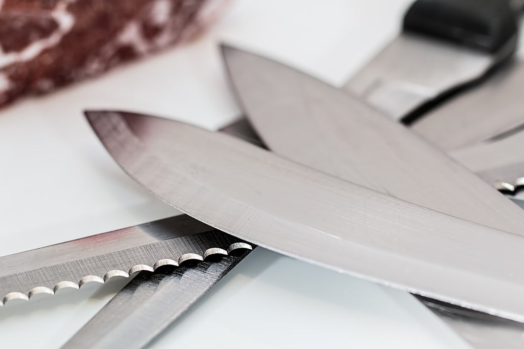 Serrated knife: kitchen knife blades in a pile
