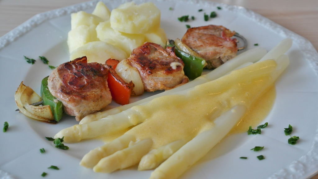 How to cut asparagus: whole white asparagus spears plated with grilled meat