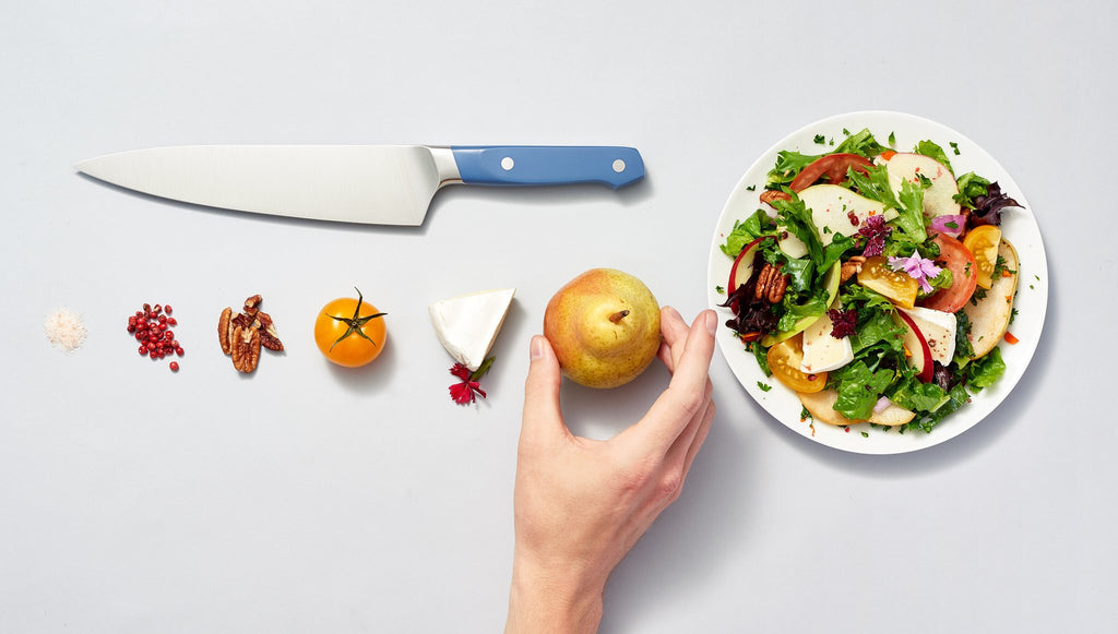 Chopped vs. diced: Chopped ingredients, a knife, a salad, and a hand holding a pear