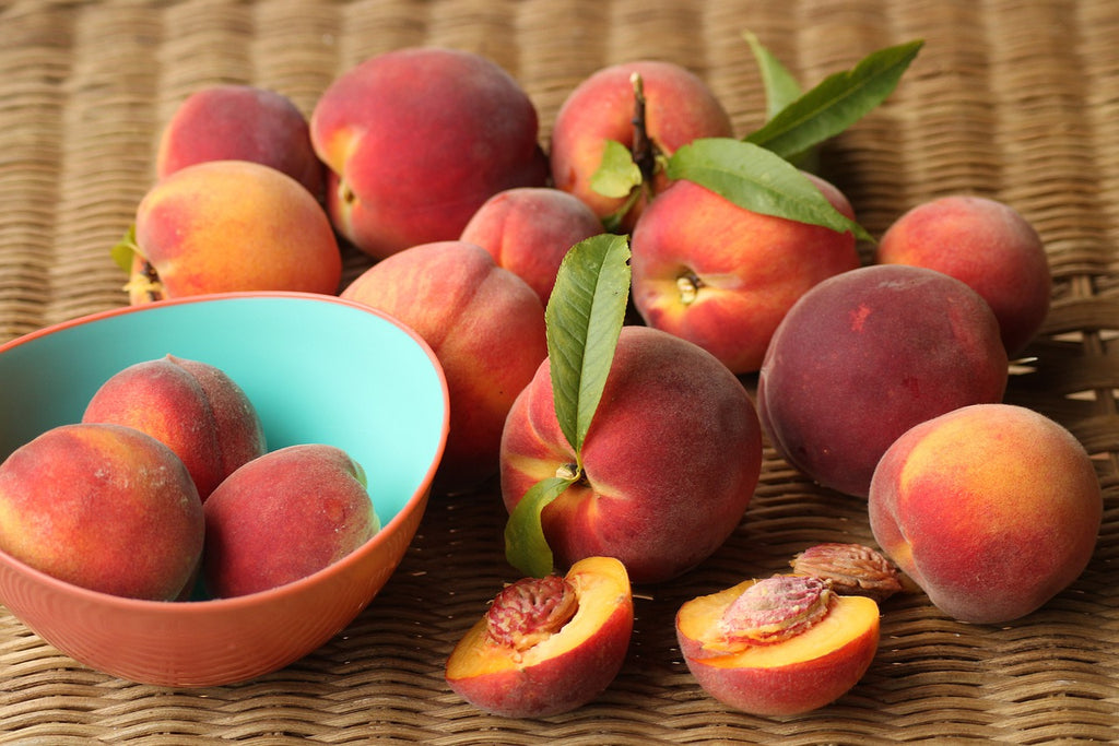 How to cut a peach: a group of peaches with some sliced and some in a bowl