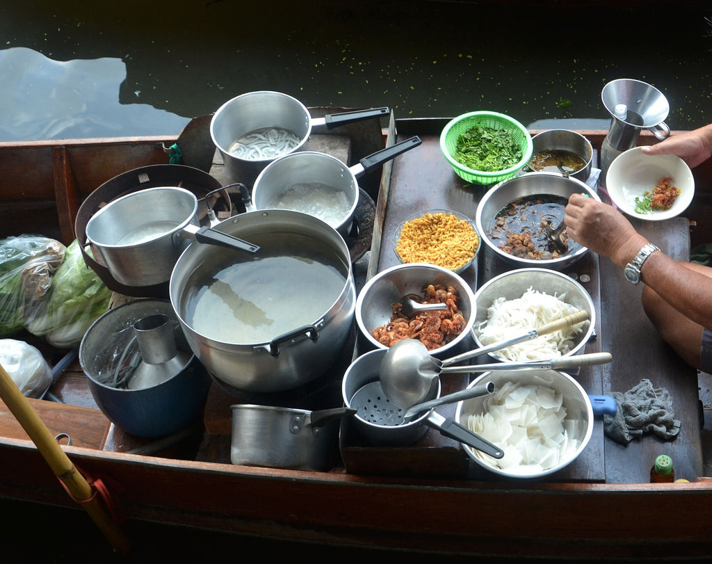 Small saucepan: many sauce pans being used for different purposes on a floating food stall