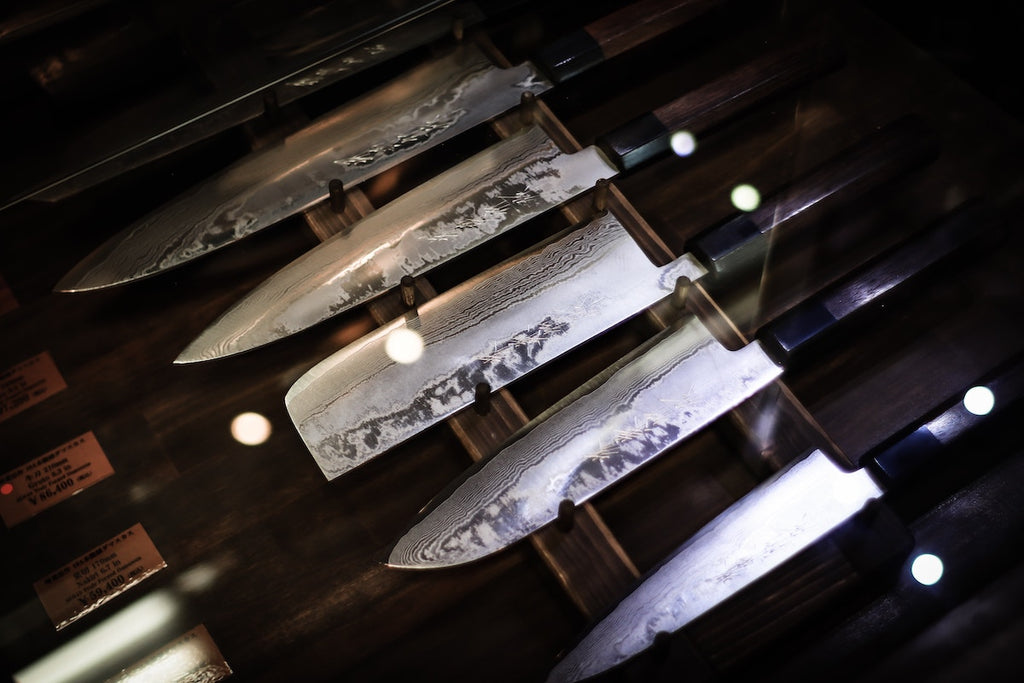 Japanese kitchen knives: a collection of Japanese knives with a petty knife closest to the frame