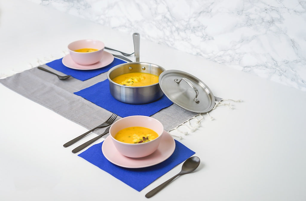 Types of pans: a stainless steel saucier and two bowls of soup