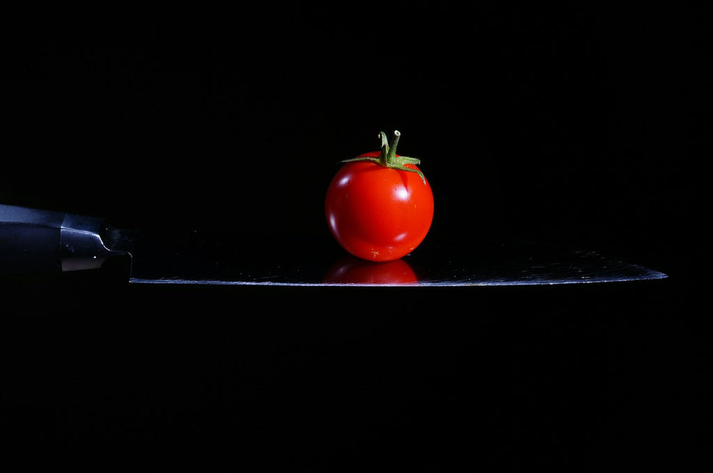 Knife sharpening stone: a tomato balanced on a knife