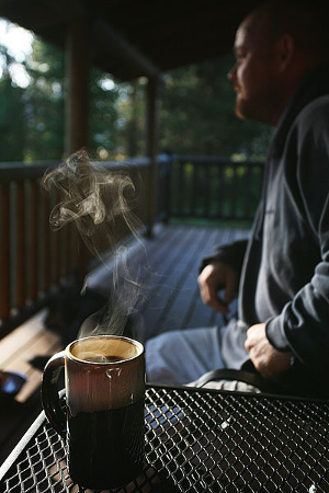 Photo of a man on a porch in the morning with a steaming cup of coffee