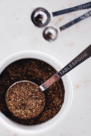 Photo of ground coffee in a white cup and measuring spoons