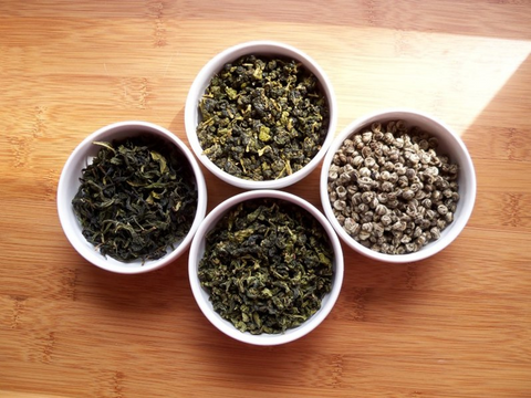 Four small white bowls filled with loose leaf tea