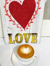Photo of a bag with a red heart and the word LOVE on Gold Letters and a Latte Art Coffee