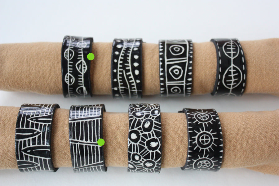 Eight black and white napkin rings with napkin