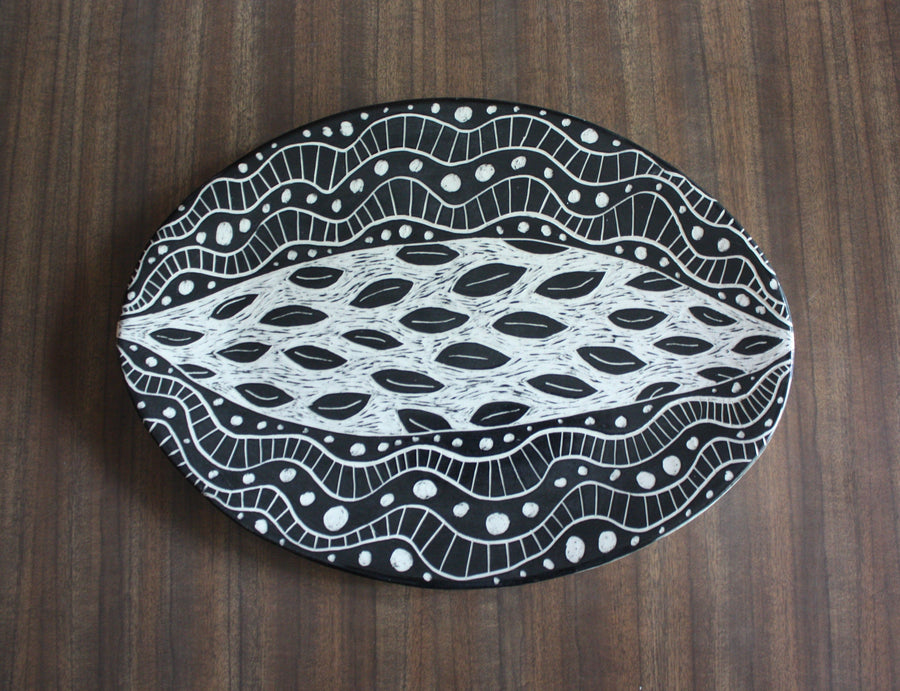 hand holding large oval serving platter horizontally