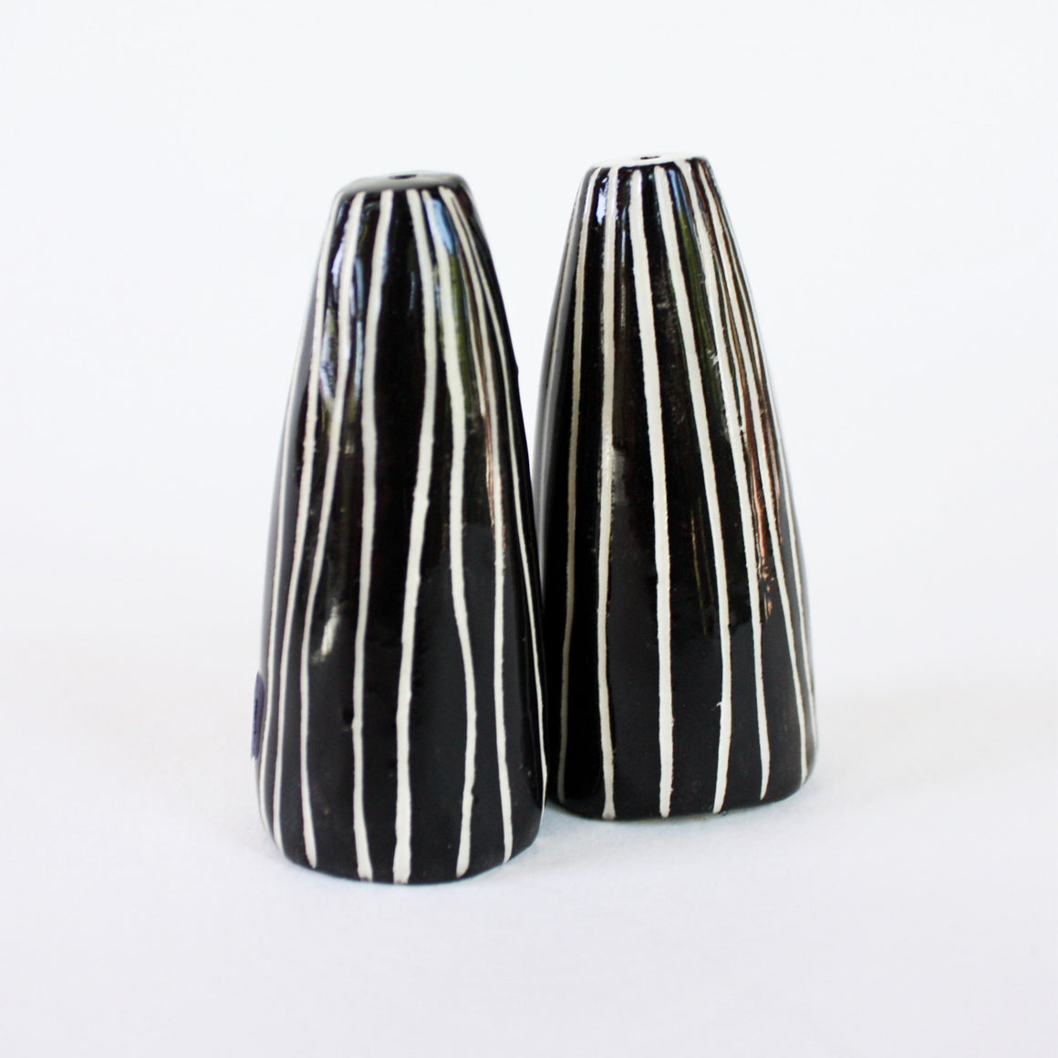 Pair of black and white salt and pepper shakers with skinny white stripes