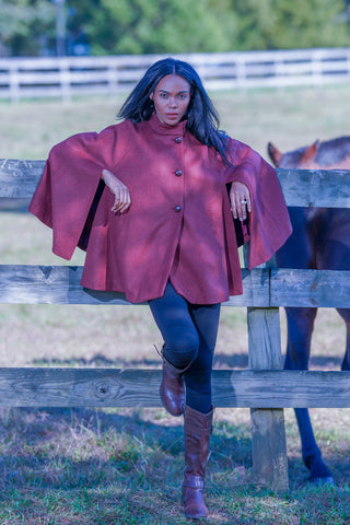 young woman wearing Robert W. Stolz poncho in cherry red