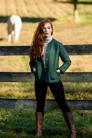 young women with red hair standing in front of pasture wearing green boiled wool jacket from Robert W. Stolz