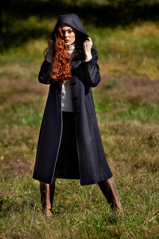 young lady standing in pasture wearing Robert W. Stolz hooded wool coat