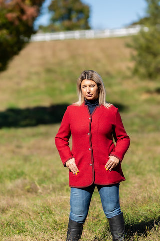woman wearing red austrian boiled wool jacket with maroon trim from Robert W. Stolz standing in a horse pasture in Potomac Maryland