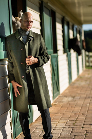 man wearing traditional austrian loden hunting coat in green at horse stable in Potomac Maryland