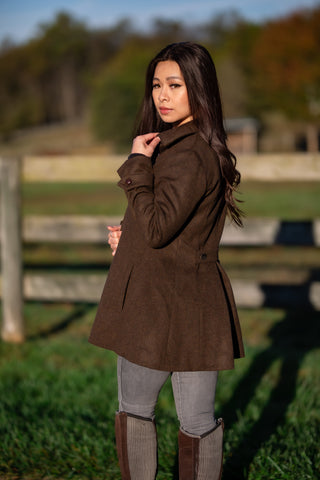 young woman wearing bark brown Robert W. Stolz loden wool coat in front of fence
