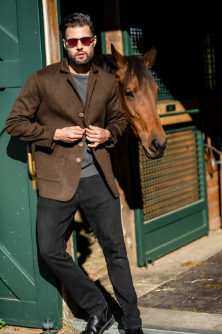 young man wearing Robert W. Stolz loden blazer at luxury stables