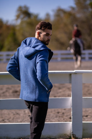 young man wearing blue boiled wool hoodie from Robert W. Stolz watching a horseback rider in Potomac Maryland