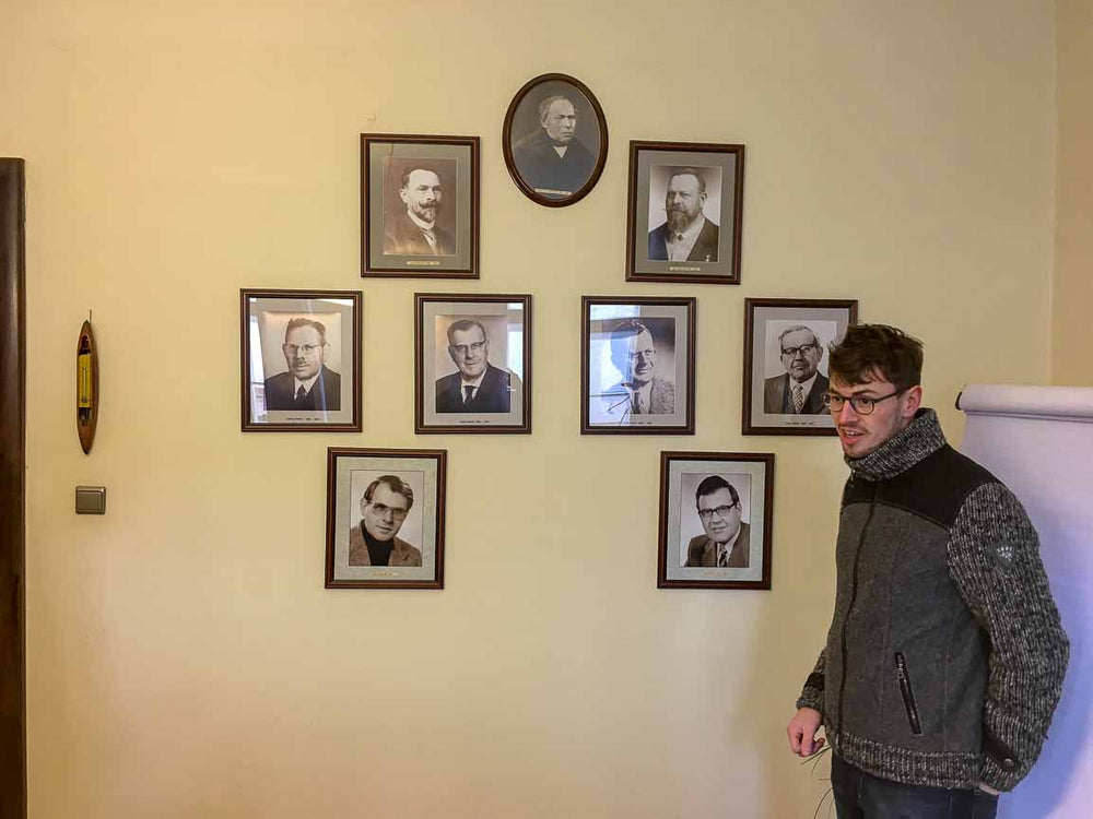 Maximilian Mehler standing in front of pictures of his ancestors who ran the family owned and operated mill before him in Bavaria, Germany