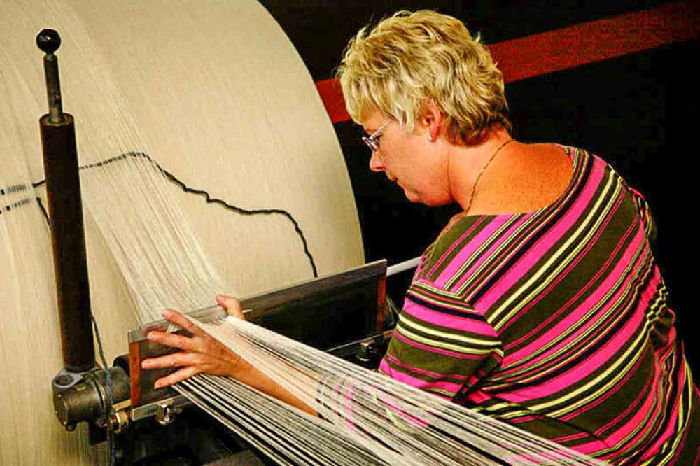 german woman preparing the warp for a loden fabric at the German tradtional Mehler mill