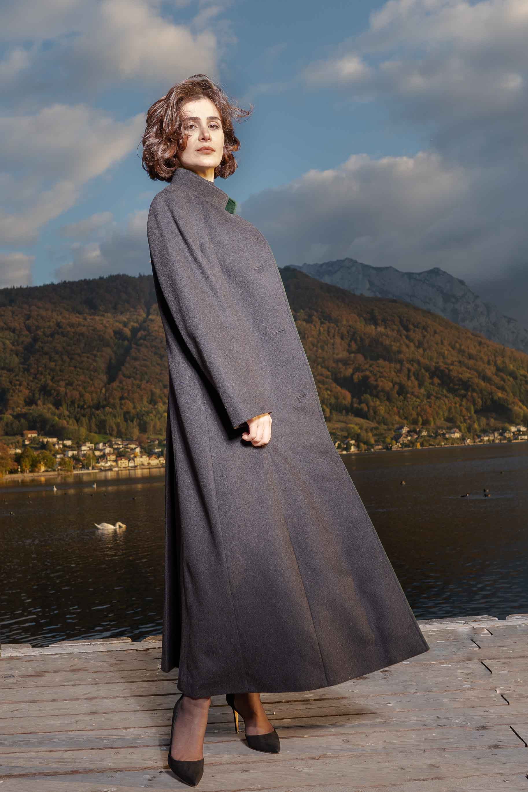 young women wearing a full length Robert W. Stolz wool overcoat standing on a pier by a lake in Gmunden