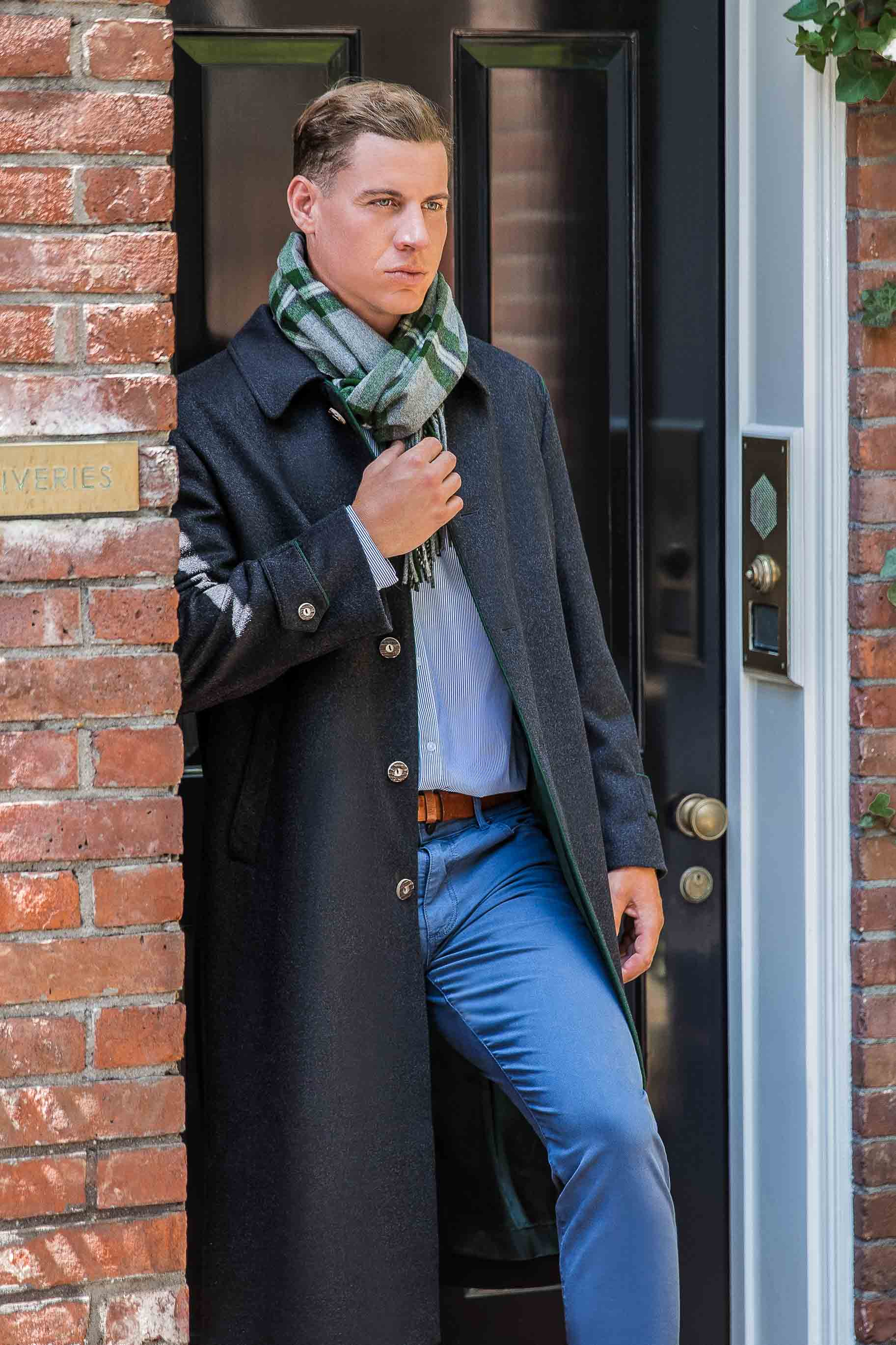 young man wearing a Robert W. Stolz classic loden overcoat standing in doorway of house in New York City