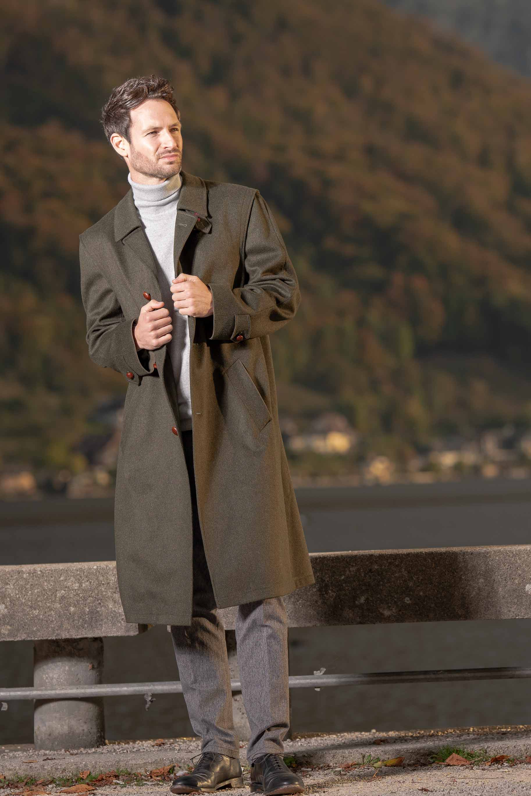 young man wearing Robert W. Stolz traditional Austrian hunting loden wool coat standing by a lake in Gmunden, Austria