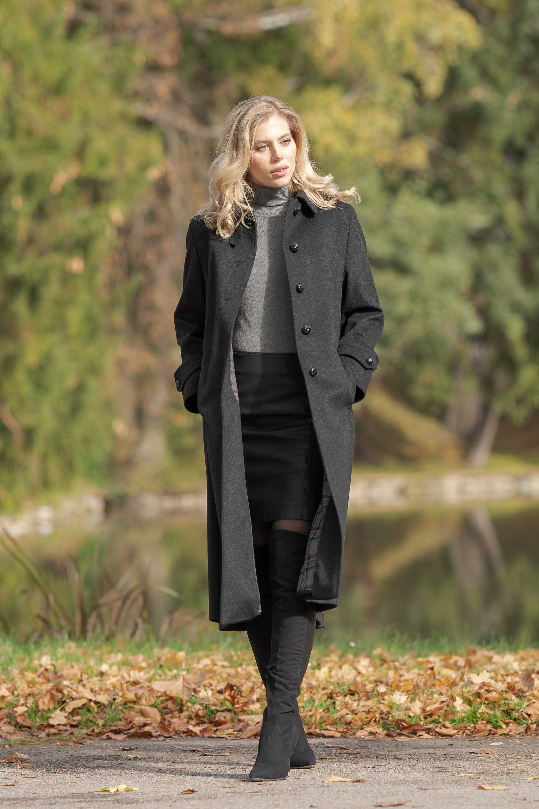 young blonde women wearing a Robert W. Stolz charcoal loden coat standing by a pond in Fall weather